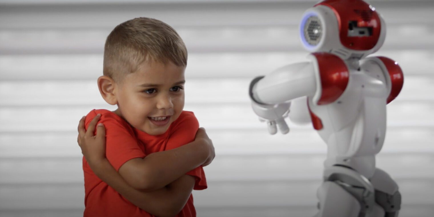 Young boy interacting with a small humanoid robot - play video