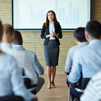 Business woman giving a presentation to a crowd