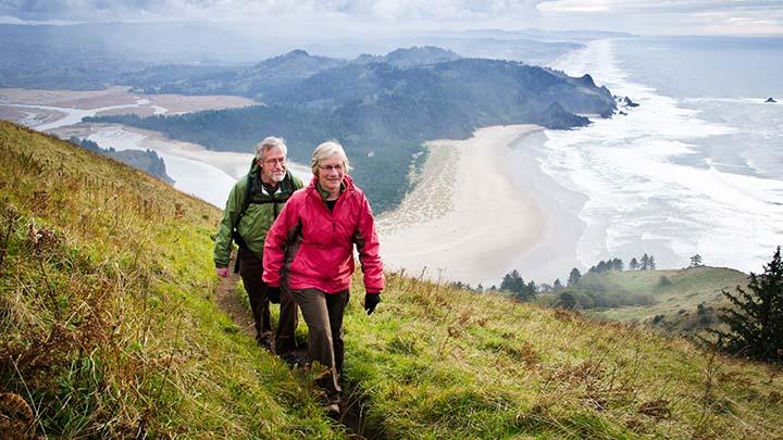 Senior couple hiking above coast